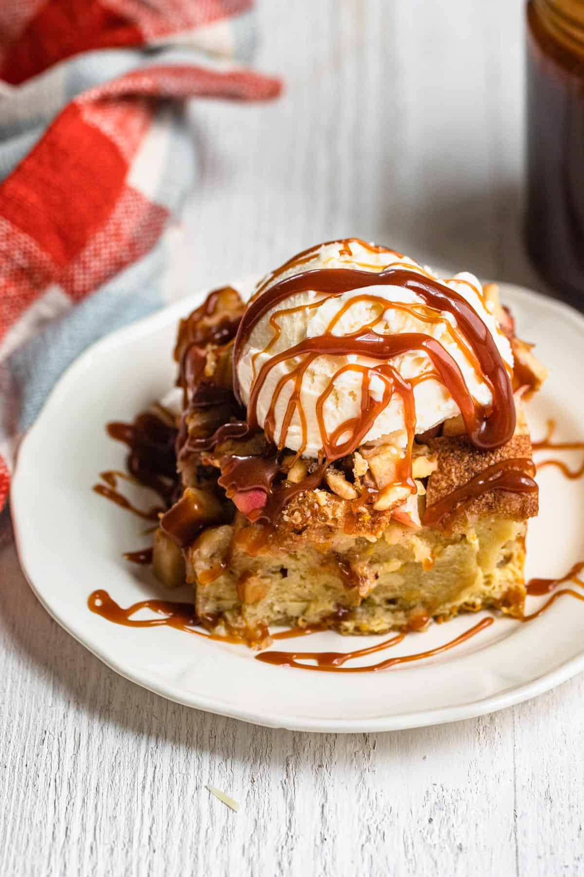 Plate of the apple bread pudding with ice cream on top and caramel sauce drizzle over