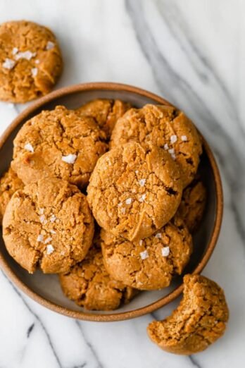 Bowl of the gluten free peanut butter cookies with a bite taken out of one of them