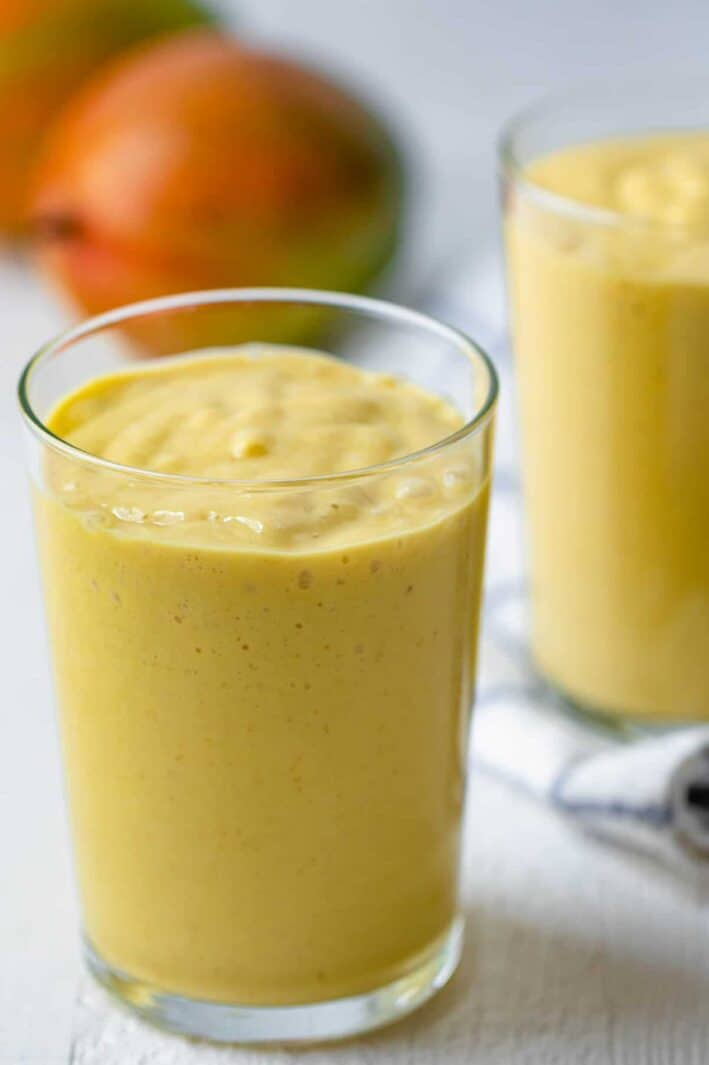 Tall glass of mango smoothie with mangos in background