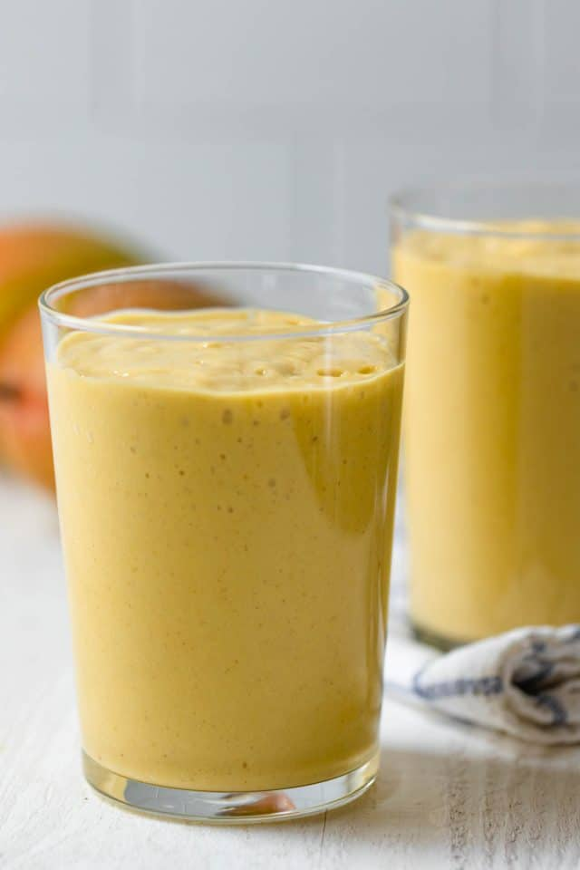 Two clear glasses of mango smoothi