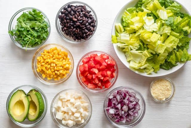 Ingredients to make the salad all in individual clear vowls