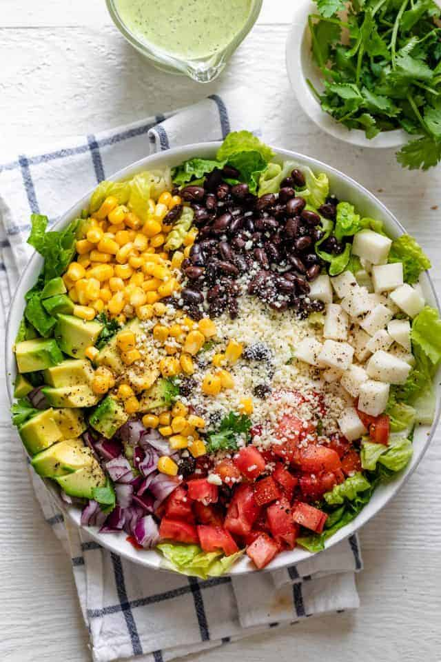 Mexican chopped salad in a large bowl with dressing on the side along with cilantro