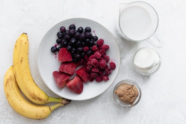 Ingredients to make the recipe: bananas, berries, milk, greek yogurt and almond butter