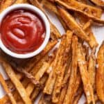 A pile of Crispy oven baked french fries with ketchup in the middle