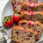 Plate of slices of strawberry banana bread with fresh strawberries on the side