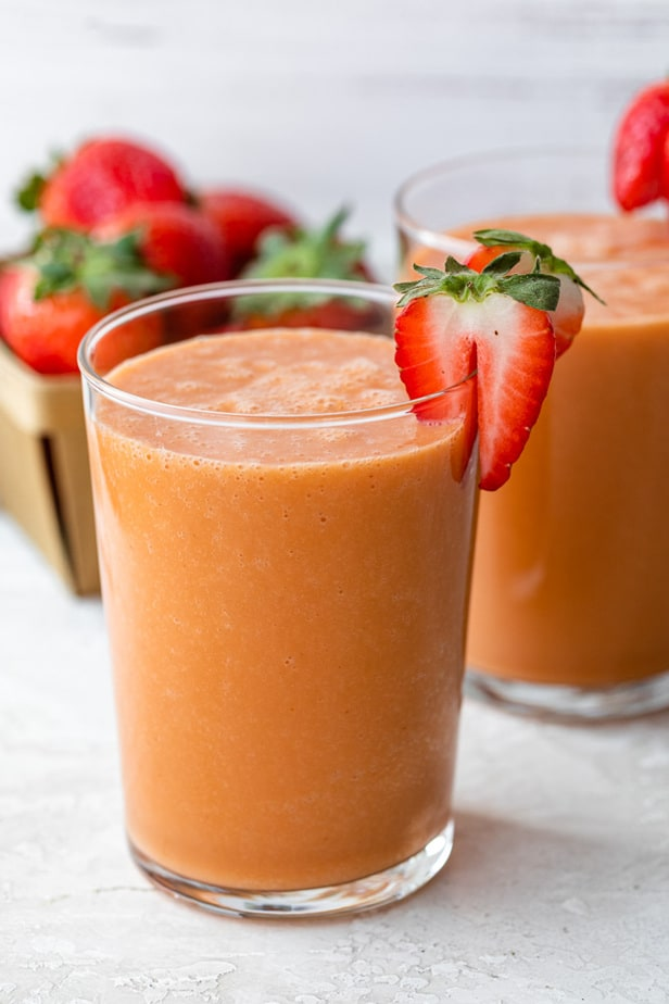 A strawberry mango smoothie garnished with a fresh strawberry