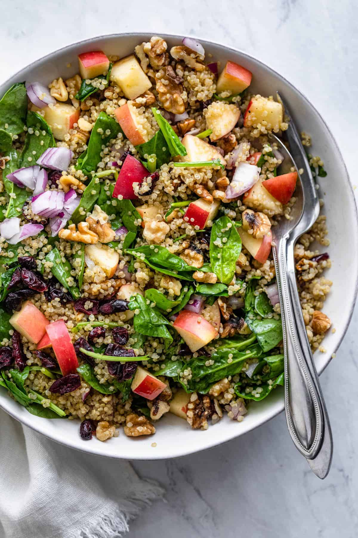 Walnut apple quinoa salad serve in a large bowl with utensils