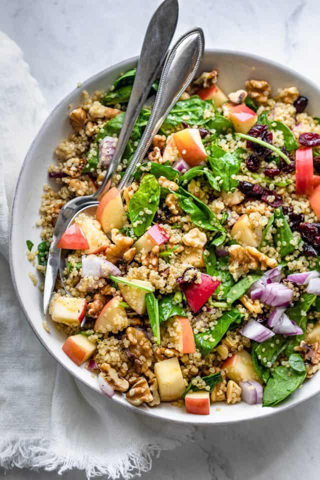 Walnut apple quinoa salad in a large bowl with serving utensils
