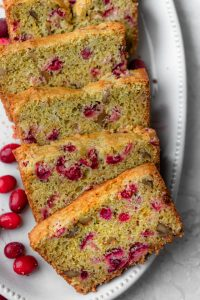 Cranberry orange bread on a white plate after sliced
