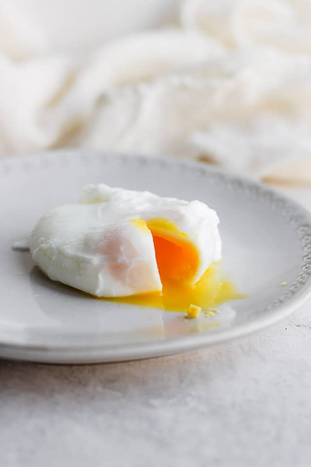 More firm poached egg on a gray plate