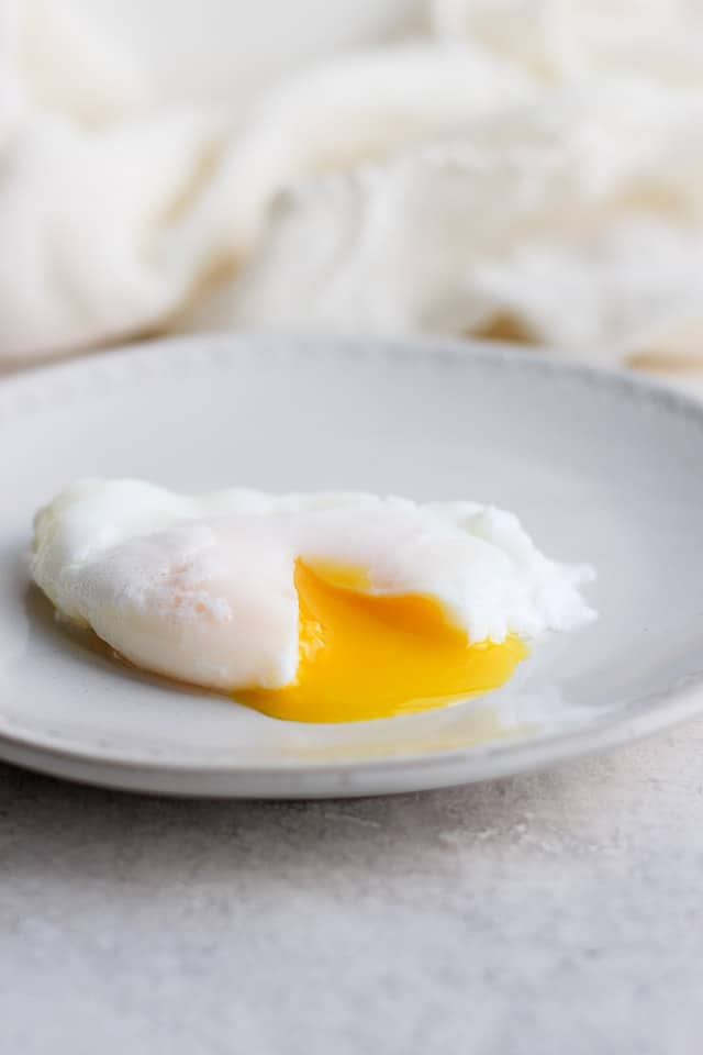 Runny poached egg on a plate