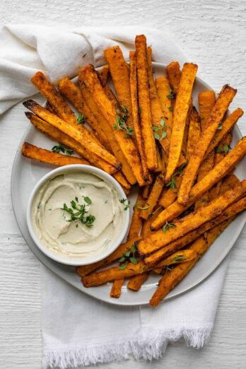 Round plate of fries with mayo dipping sauce for the butternut squash sticks