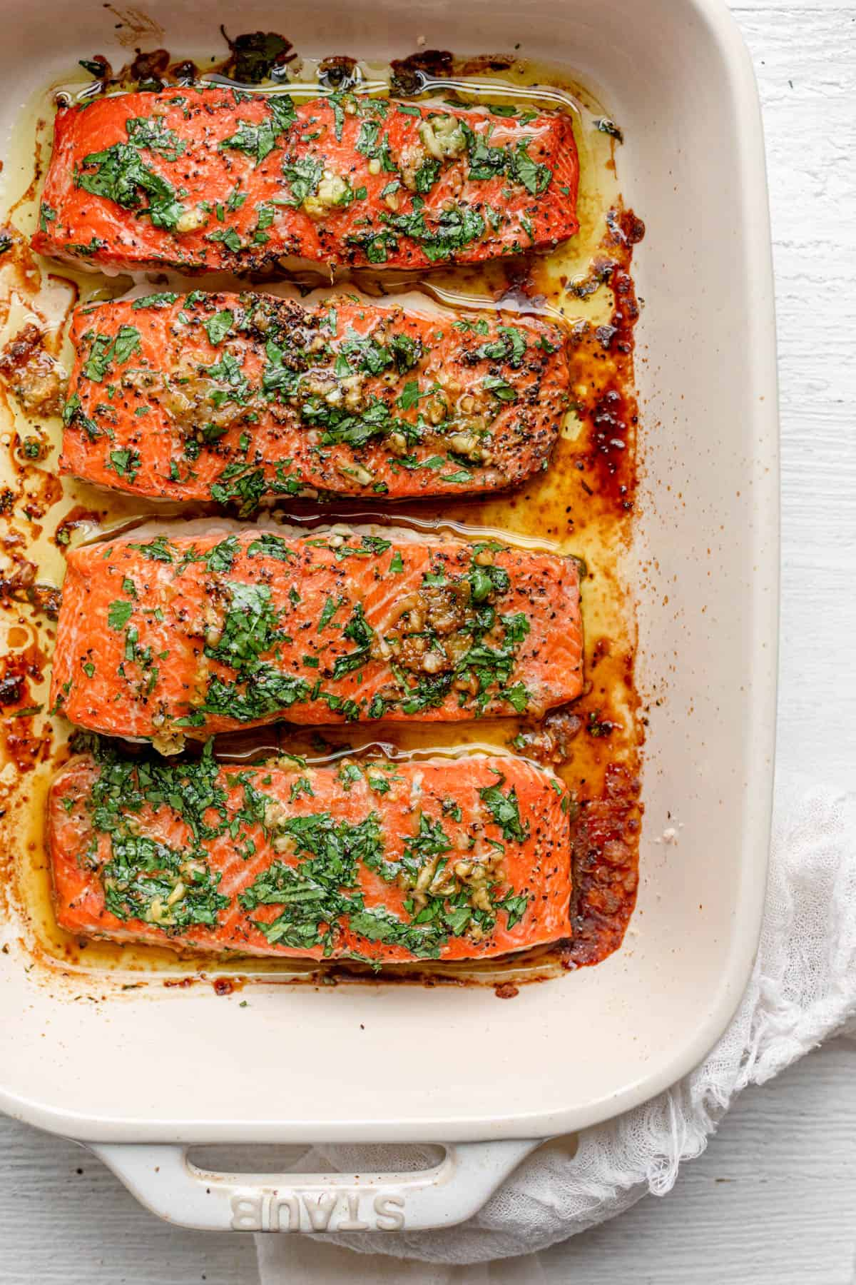 The oven cooked salmon after it's done cooking topped with garlic and cilantro in an off-white rectangle baking dish