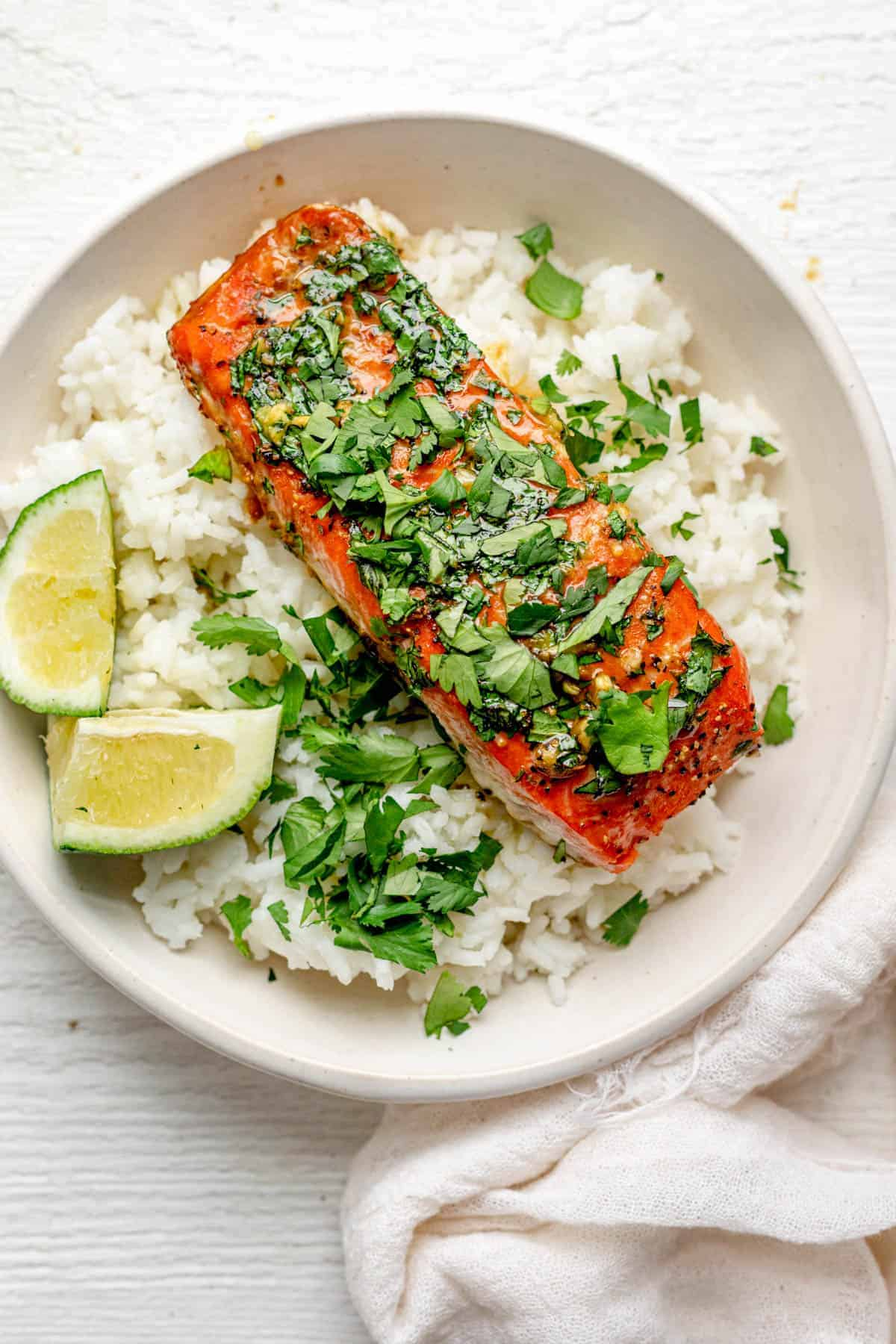 Garlic Cilantro Oven Baked Salmon in a white shallow bowl over rice with lime wedges