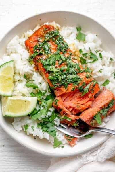 Cutting into the salmon to show how flaky it is, topped with lots of fresh cilantro over rice