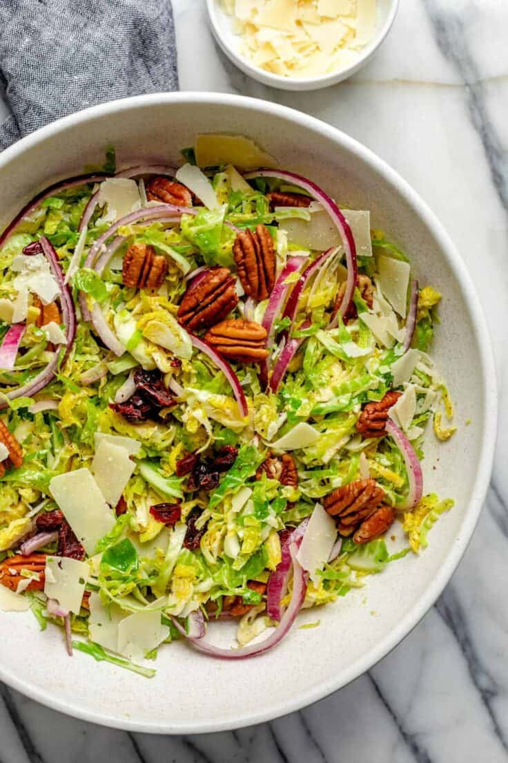 Large bowl of shaved brussel sprouts salad topped with pecans, onions, cheese, cranberries and red onions