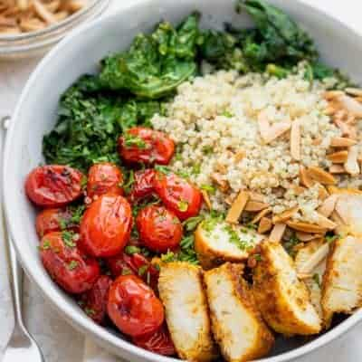 Large bowl of chicken and quinoa served with tomatoes, kale and toasted almonds