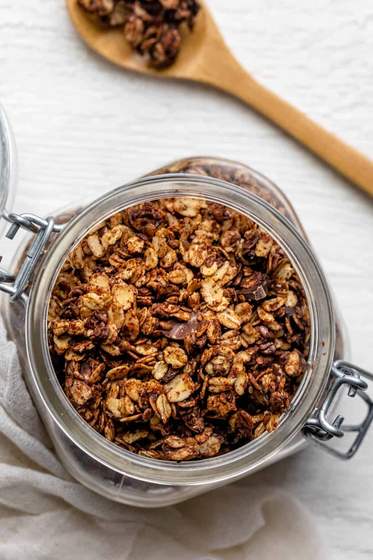 Jar canister of chocolate granola with wooden spoon on side with granola on it