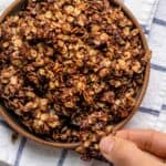 Shallow bowl of homemade chocolate granola with fingers grabbing large chunk