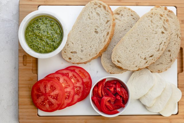 Ingredients to make the recipes: bread, pesto, mozzarella cheese, tomatoes and roasted red peppers