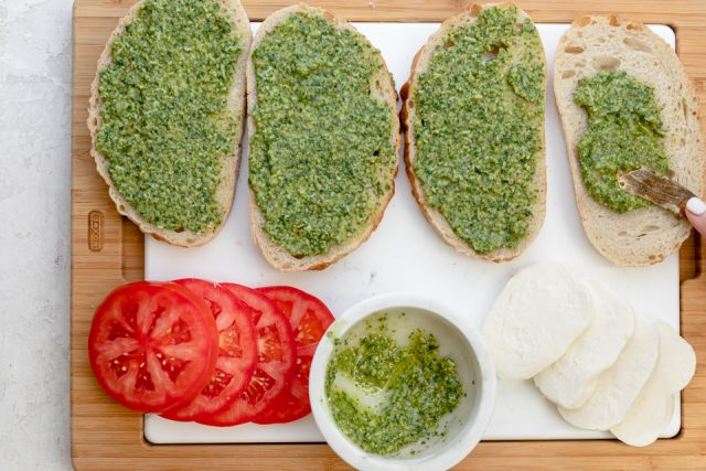 Spreading walnut pesto on the bread before assembling and grilling