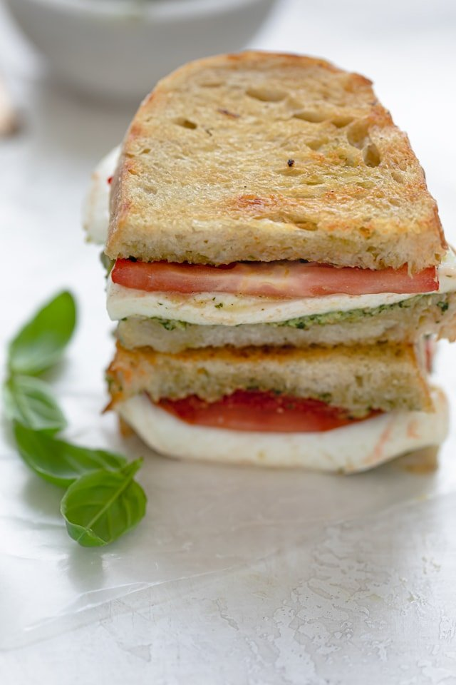 Mozzarella Grilled Sandwich stacked with basil on the side