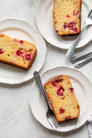 Three slices of lemon cranberry cake on small white plates with forks