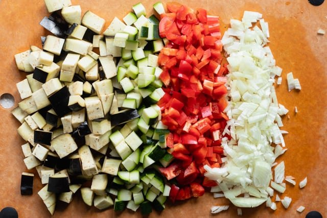 Vegetables chopped for the recipe: eggplant, zucchini, red peppers and onions