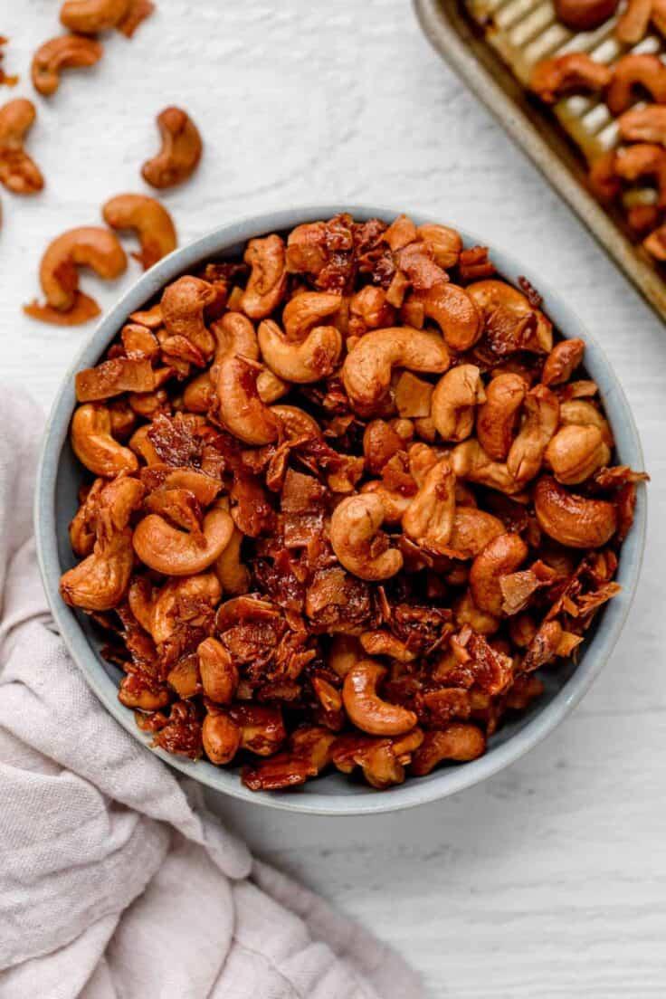 Large bowl of roasted cashews with coconut on white background