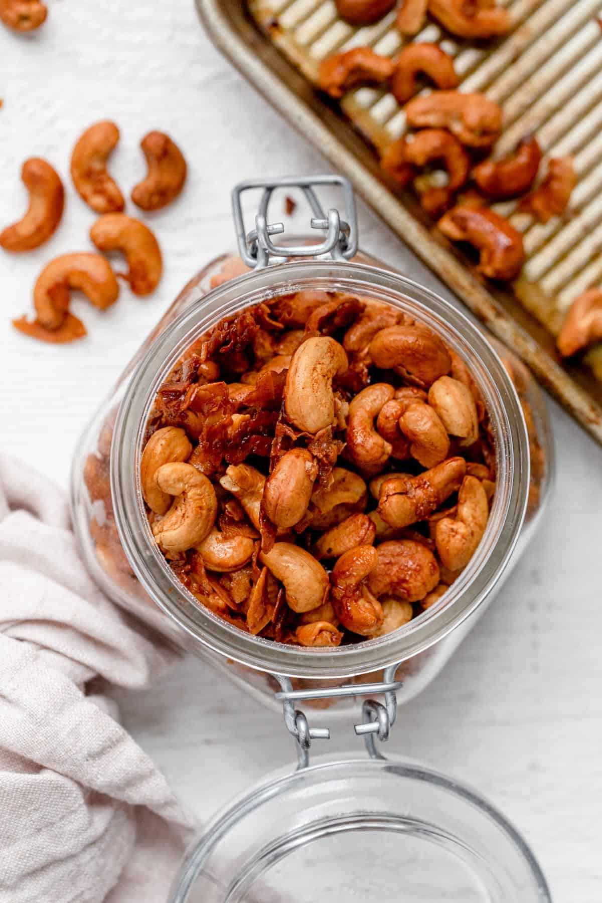 Roasted cashews stored in open glass jar with baking pan and cashews next to it
