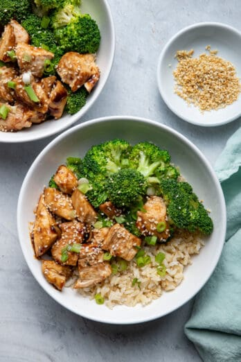 Chicken Teriyaki, Brown Rice and Broccoli in bowls with sesame seeds on the side