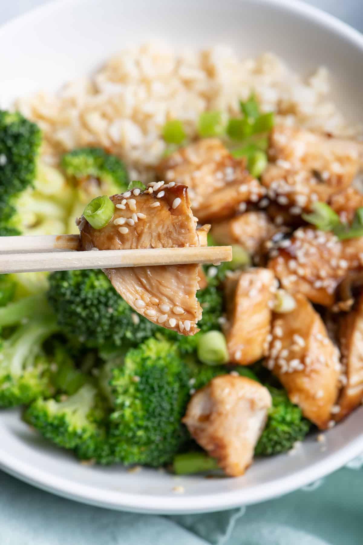 Close up shot of chopsticks picking up cubed chicken in chicken teriyaki bowl