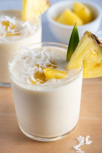 Two small cups of pina colada smoothies with pineapples on on the cup