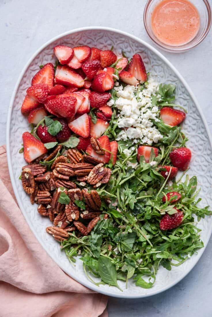 Strawberry Arugula Salad on a large platter with the dressing in a small bowl next to it