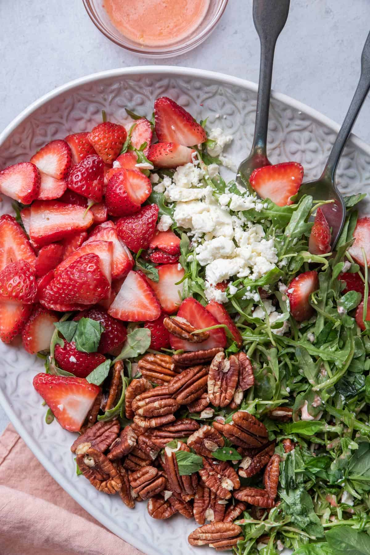 Close up shot of the strawberry arugula salad with fork and spoon for serving