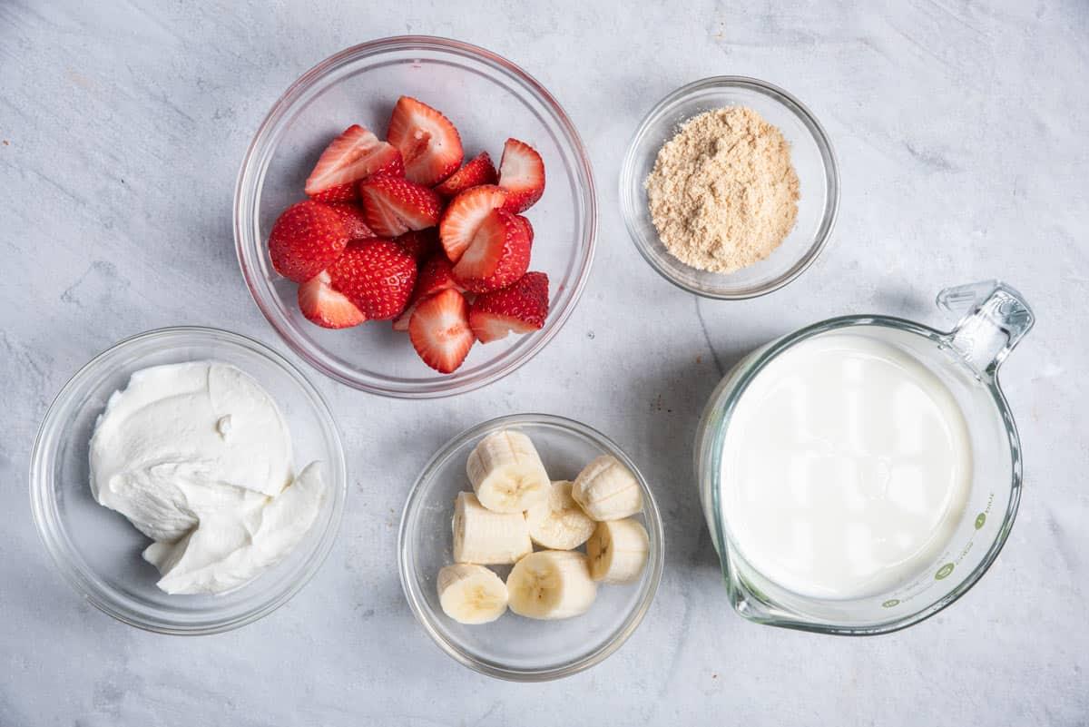 Ingredients to make the smoothie: milk, strawberries, banana, greek yogurt and protein pwoder
