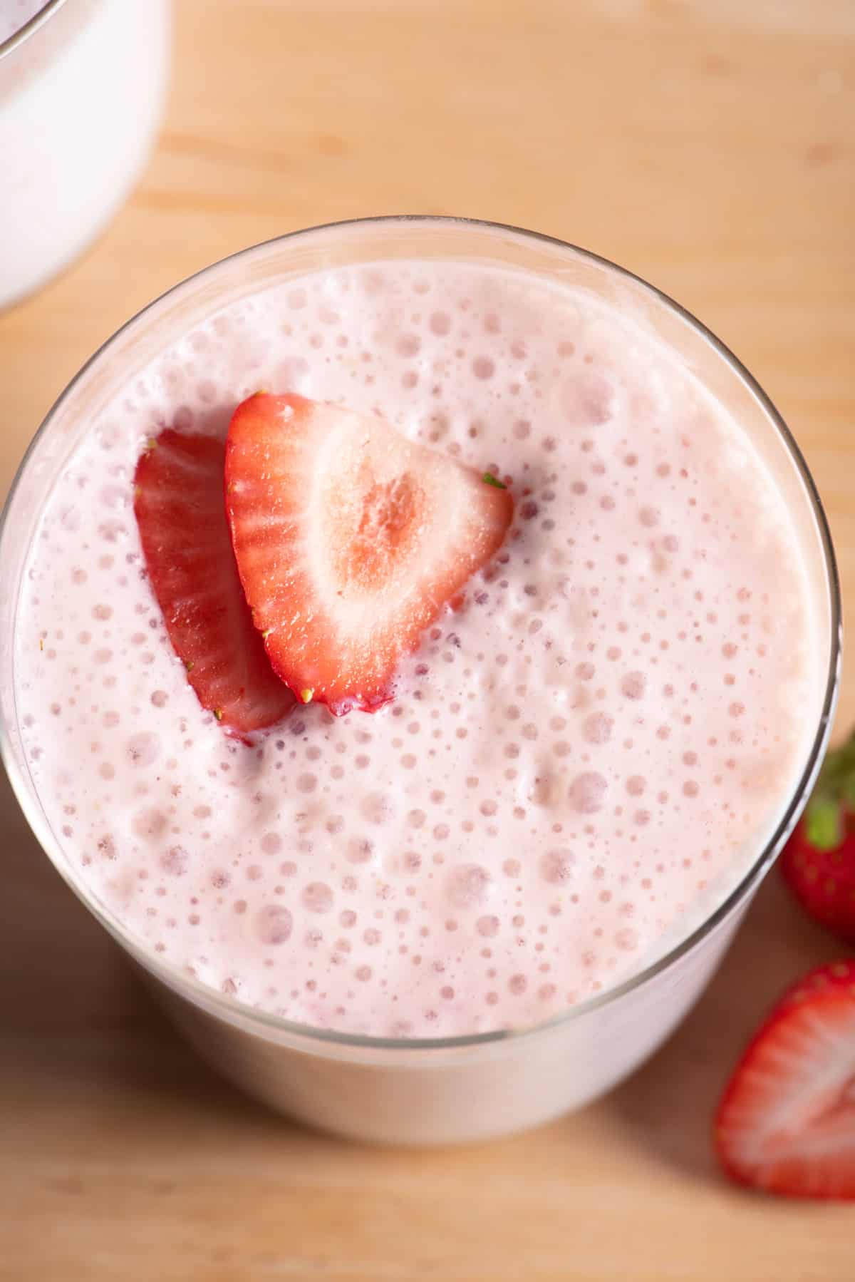 Top down view of strawberry protein smoothie with slices of strawberries on top