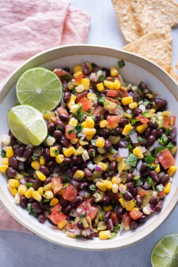 Black bean salsa with limes served with chips on the side