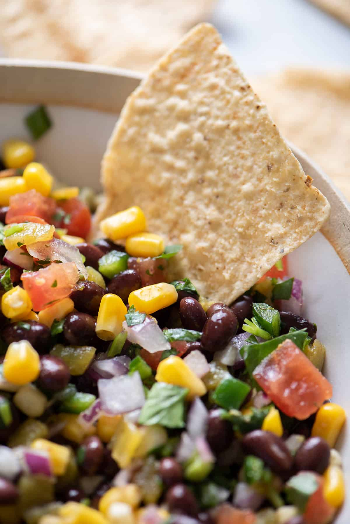 Close up shot of black bean salsa with chip dipping in