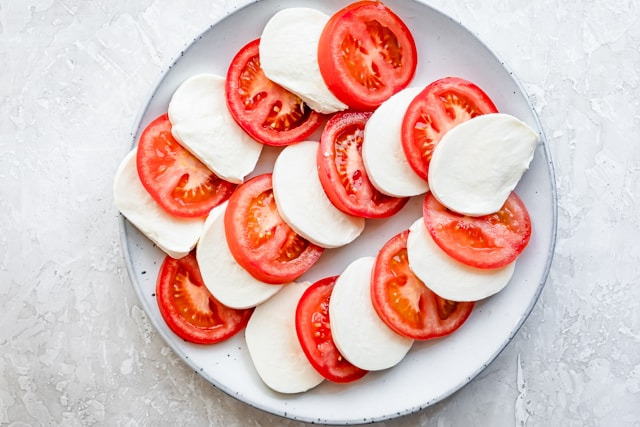 Alternating tomat and mozzarella slices on a serving platter