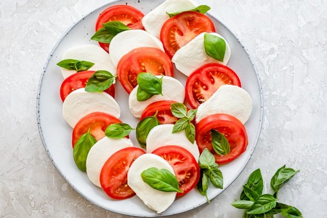 Alternating tomato and mozzarella slices with basil on serving platter