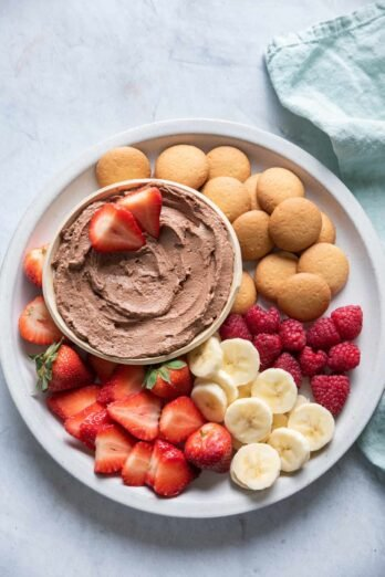 Chocolate Peanut Butter Dip on a plate with fruit and wafers for dippings