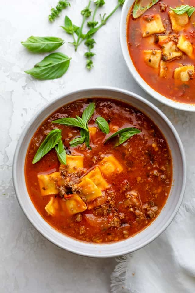 Large bowl of ravioli soup made with ground beef and garnished with basil