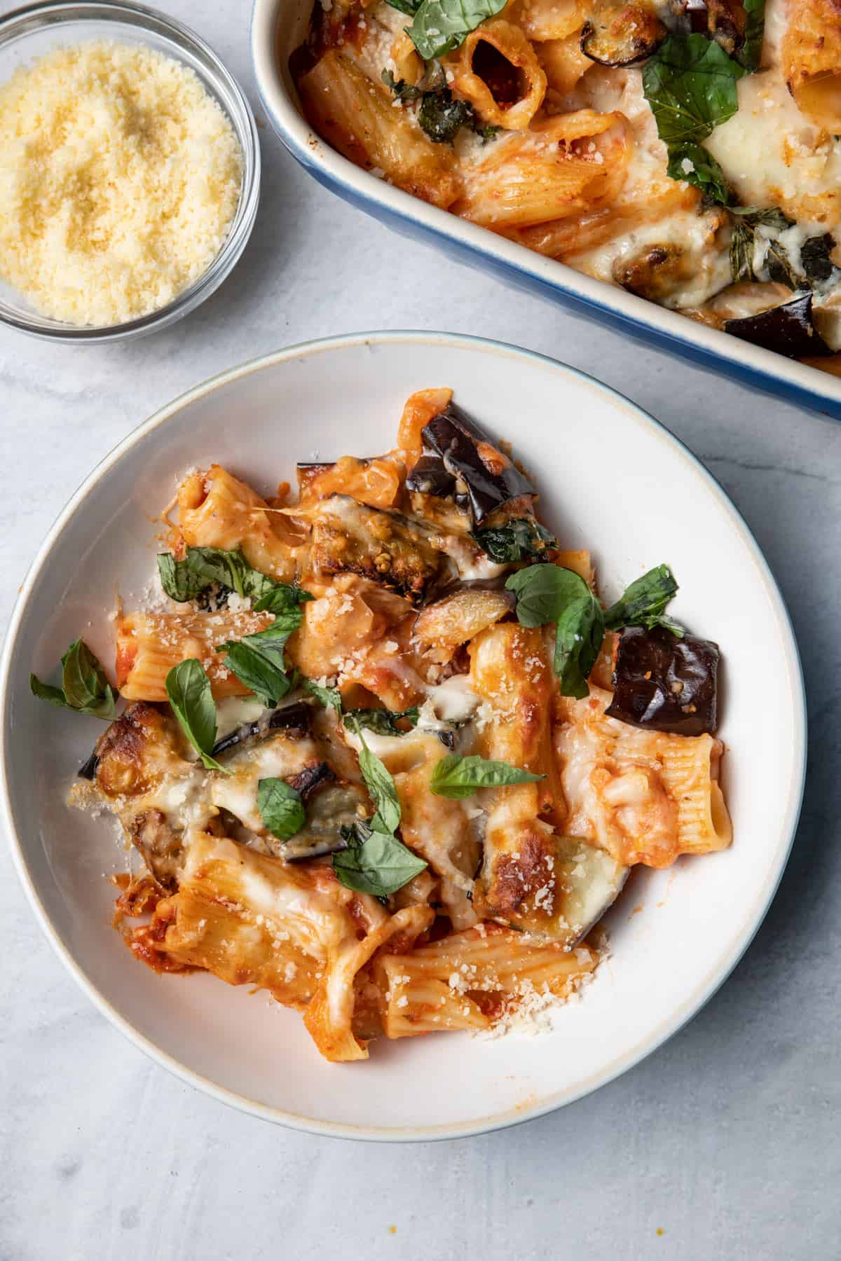 Eggplant pasta casserole served in a small bowl with parmesan cheese on the side
