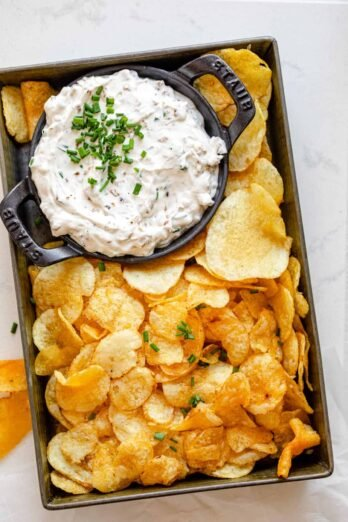 Homemade french onion dip in a small bowl with potato chips around it in small tin