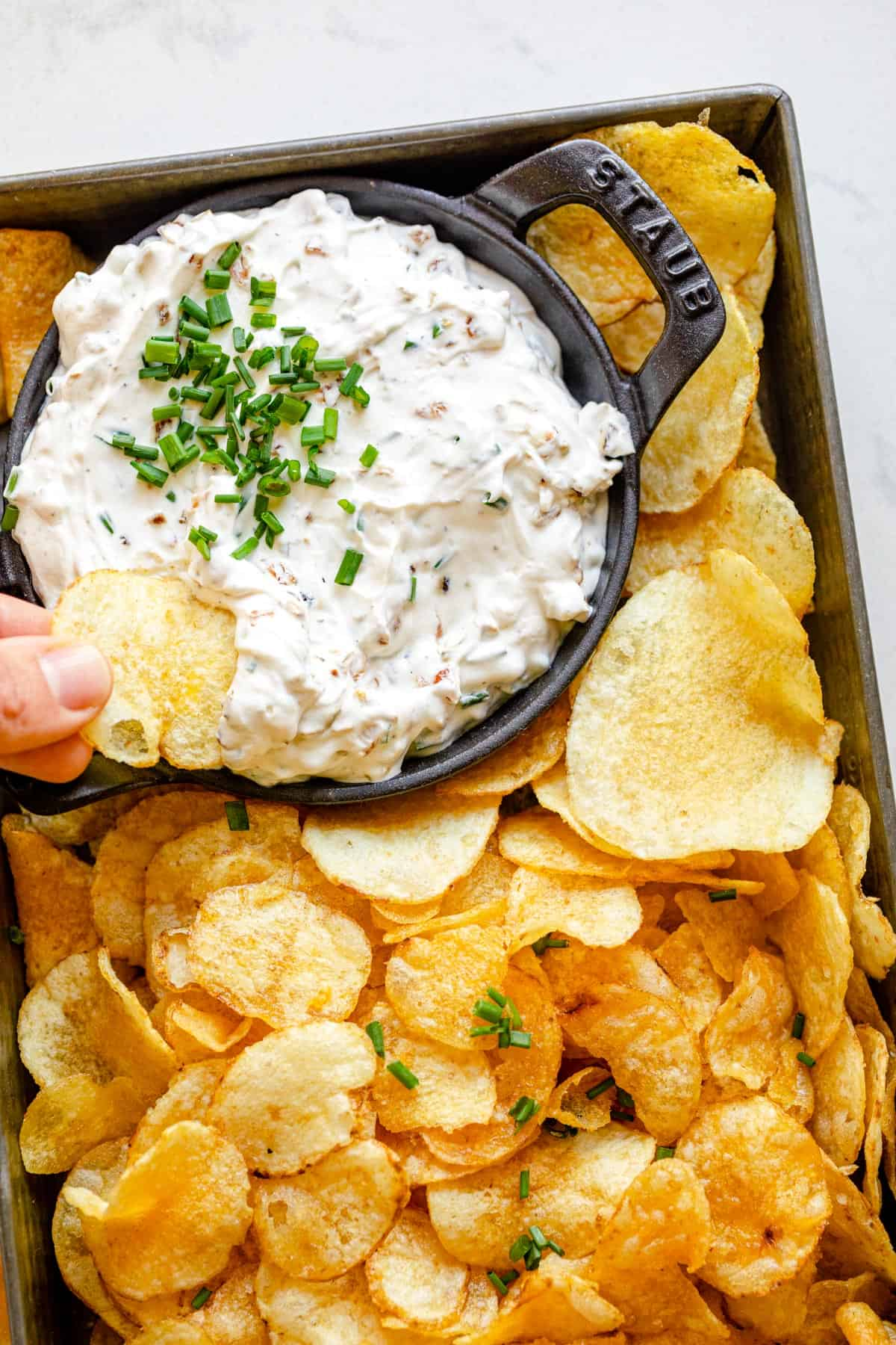 Close up shot with potato chip dipping into french onion dip