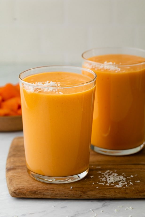 Two cups of mango papaya smoothie topped with shredded coconut