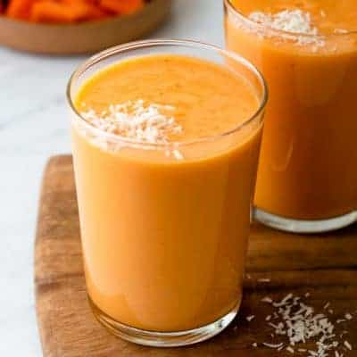 Mango papaya smoothies in clear cups with bowl of papaya in the background