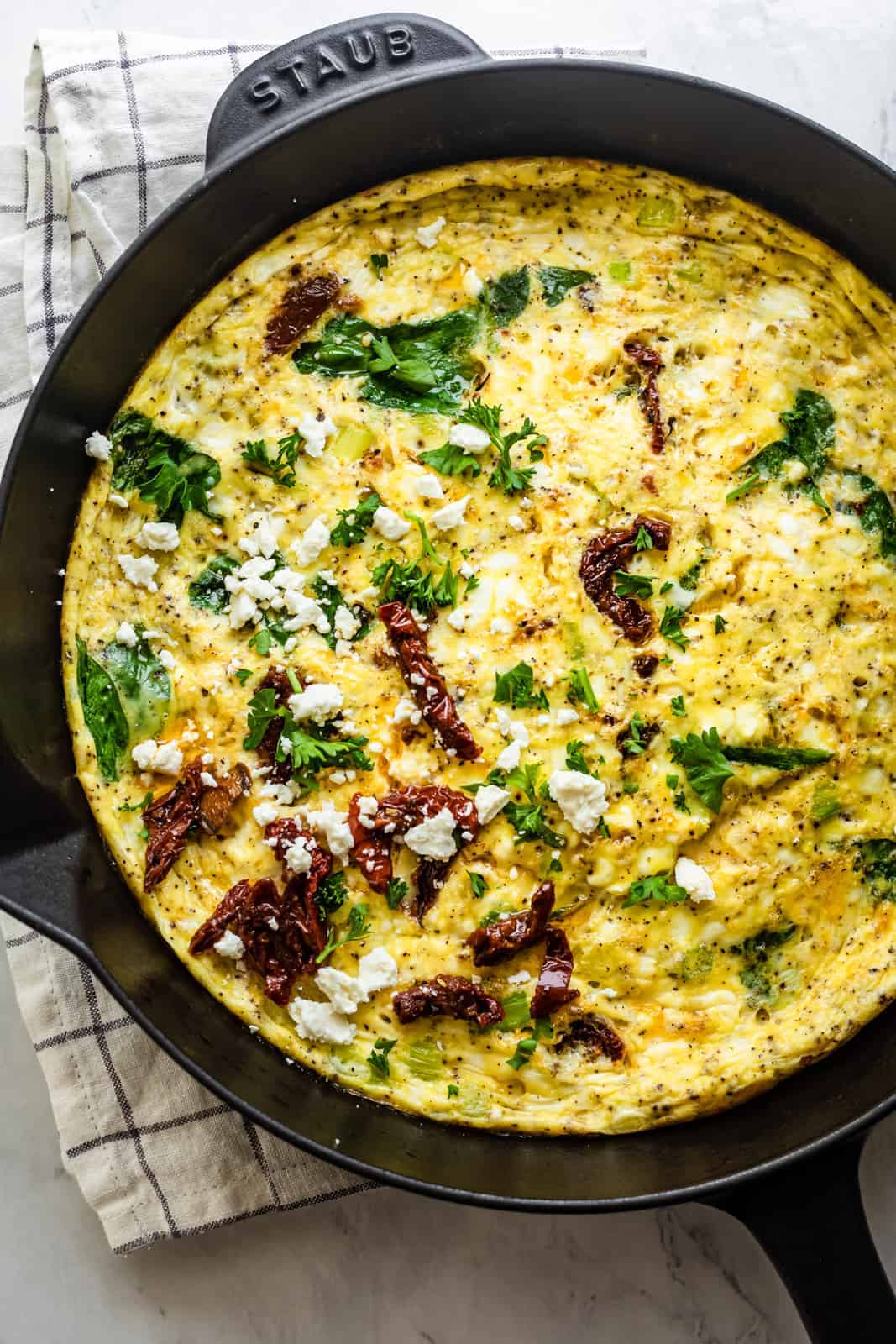 Mediterranean Frittata in a cast iron skillet topped with sundried tomatoes, feta cheese and parsley