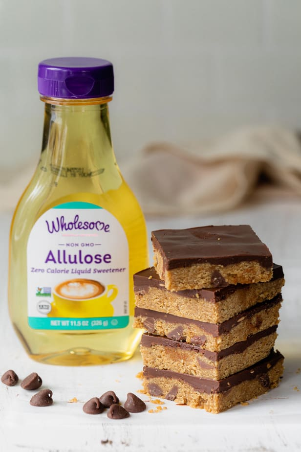 Stack of cookie dough bars with bottle of sugar free Wholesome Allulose next to them - used to make them